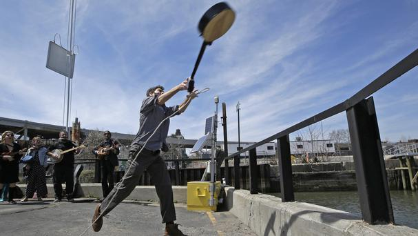 Event founder Eli Smith tosses a banjo during the Brooklyn Folk Festival's Gowanus Banjo Toss (AP)
