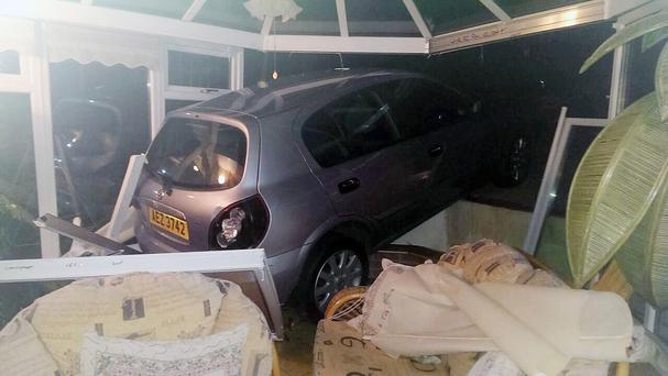 A car rolled backwards off a driveway, through a neighbour's fence and over a garden pond before smashing into a conservatory (Burke Brothers Recovery/PA)