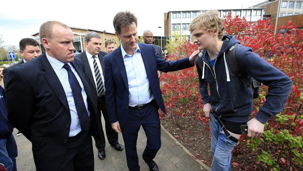 Liberal Democrats leader Nick Clegg passes a young man in the process of pulling his jeans up