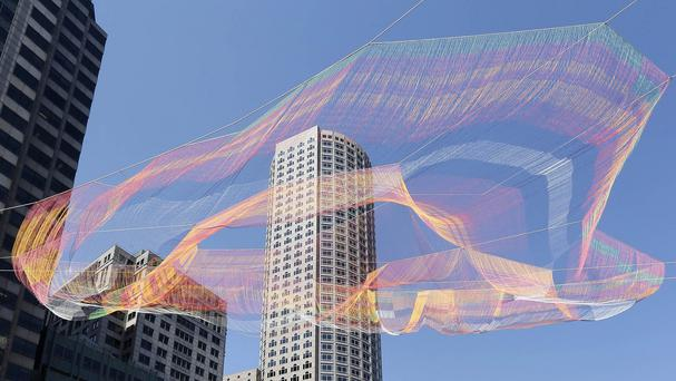A colourful 600-foot sculpture is suspended between high-rise buildings above the Rose Kennedy Greenway in Boston (AP)