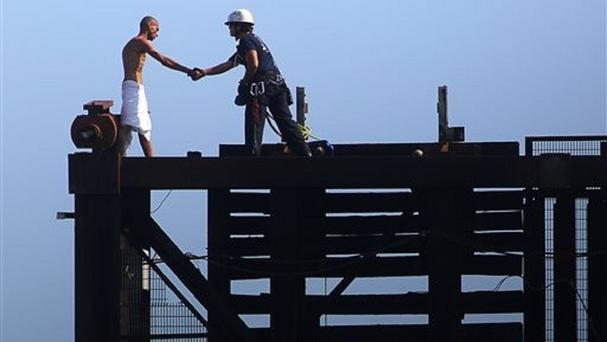 A member of the Fort Lauderdale fire department rescues a man on top of a raised drawbridge (Michael Clary/South Florida Sun-Sentinel via AP)