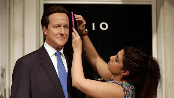 Caryn Mitman puts the finishing touches on a refresh of Prime Minister David Cameron's wax figure at Madame Tussaud's in London, five years after its original inclusion and ahead of the Queen's speech. (PA)