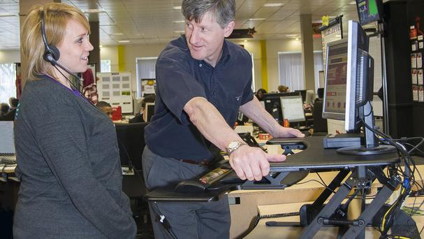 Dr John Buckley with Virgin Media Angel Gemma Winslade at an adjustable height desk (Virgin Media/PA)