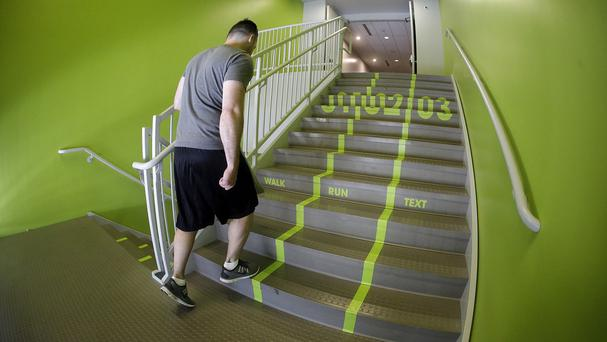 A Utah Valley University student walks up the bright green lanes painted on the stairs at Utah Valley University (AP)