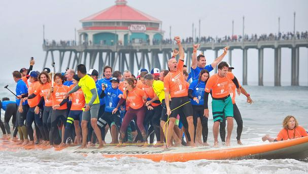 The surfers react with joy as they set a Guinness World Record for most riders on a board (The Orange County Register/ AP)