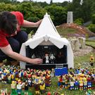 Model maker Hannah Reed adds a Lego figure of Kanye West to the Pyramid Stage at Legoland Windsor