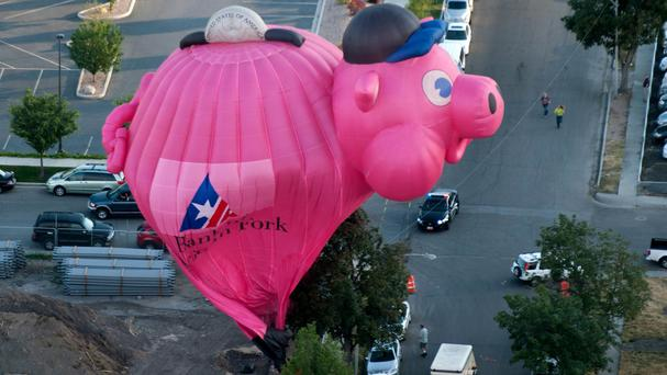 The piggy bank balloon crash lands during America's Freedom Festival Balloon Fest in Provo, Utah (The Daily Herald/ AP)