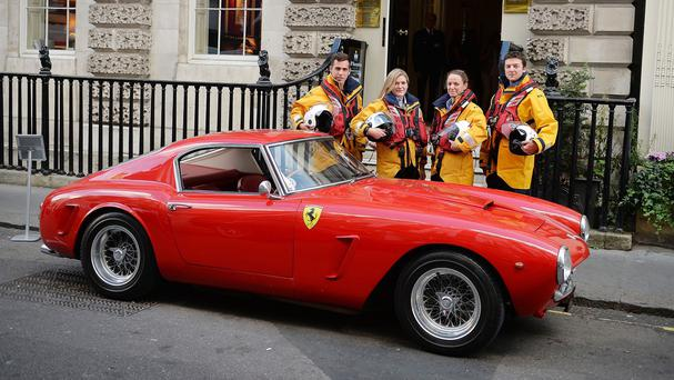 Members of the Royal National Lifeboat Institution with a red 1960 Ferrari 250 GT which is to be auctioned to raise money for the charity