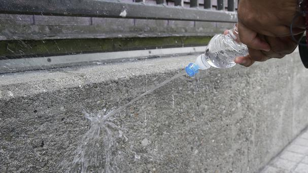 A public works employee demonstrates how water bounces off a wall covered with repellent paint outside a Mission District transit station in San Francisco (AP)