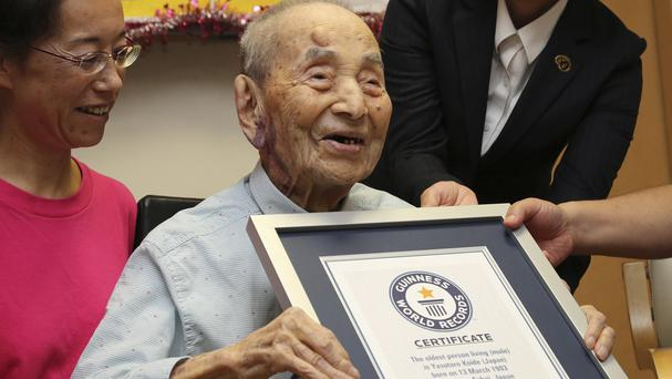 Yasutaro Koide, 112, receives the Guinness World Records certificate as he is formally recognised as the world's oldest man (AP)