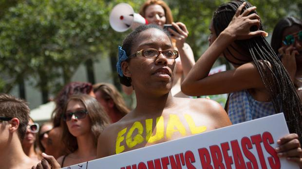 Activists hold signs during the protest march, called the GoTopless Day Parade, in New York (AP)