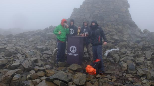 Dave Cooke, 21, Harriet Allbrook, 21, and 19-year-old Oscar Price spent nearly four hours hauling the nine gallon cask of beer to the top of Ben Nevis in Scotland (Box Steam Brewery/PA)