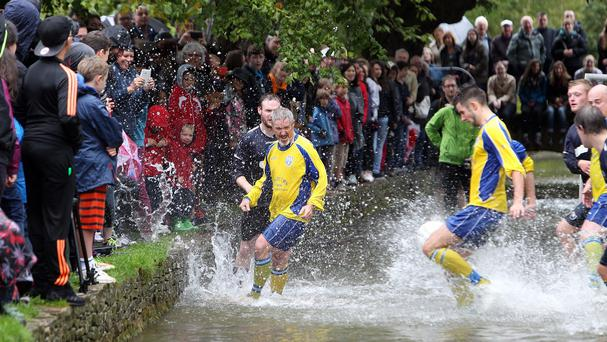 Comedian Griff Rhys Jones (centre) competes for the first eleven team, as teams from Bourton Rovers play each other in the annual traditional river football match in the Cotswould village of Bourton-in-the-Water, Gloucestershire.
