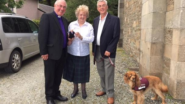 Angus Morrison, left, and Elma McArthur meet Neil Smith and bilingual dog Ginger (PA/Church of Scotland)