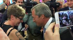Kerrie Webb shows Nigel Farage her tattoo of his face during the Ukip annual conference at Doncaster Racecourse