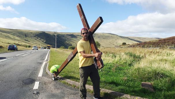 Reformed drug addict and born-again Christian Clive Cornish is walking from north to south Wales with a giant 12ft cross on his back to raise awareness for the less fortunate