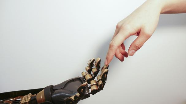 A robotic hand, with a touch-sensitive artificial skin, touching a human hand (Stanford University)