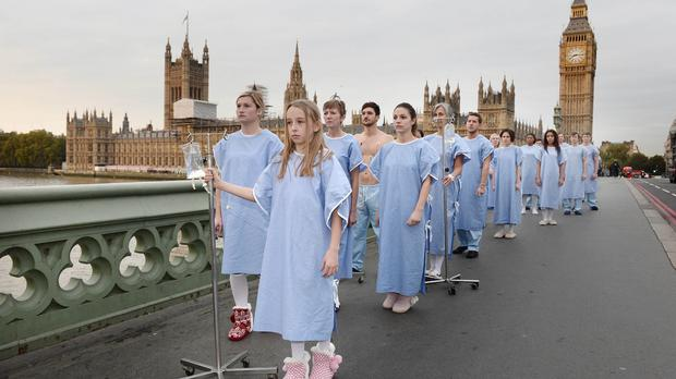 21 people dressed in surgical gowns walk among commuters on Westminster Bridge to highlight the number of patients who die every week in need of an organ transplant