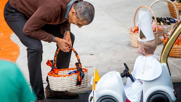 President Barack Obama laughs after greeting a child dressed as the Pope during Halloween festivities. (AP)