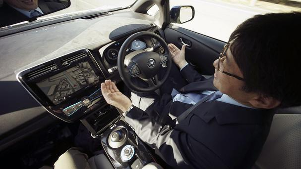 Look, no hands! Nissan general manager Tetsuya Iijima relaxes as the company's self-driving prototype vehicle does the hard work (AP)