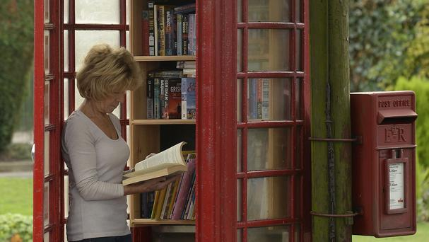 Wendy Hanlon looks at books in a red phone box which has been converted into a tiny free-to-use library in the village of Wall in Staffordshire