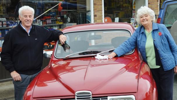 John Edwards and Doris Williams with a 1972 Saab 96 which his son bought at auction after Mr Edwards sold it as a new car in 1972 (Richard Edmonds Auctions/PA)