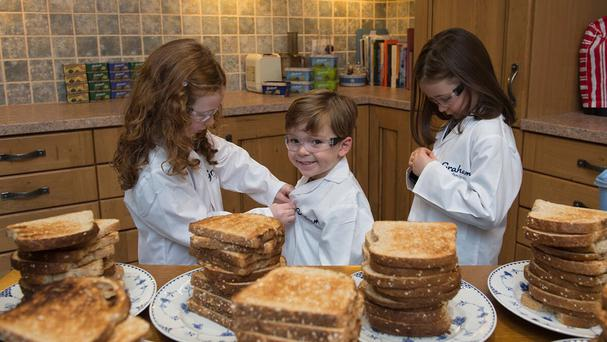 Lily, Ernie and Molly tested the theory that dropped toast always falls butter side down (Graham's The Family Dairy/PA Wire)