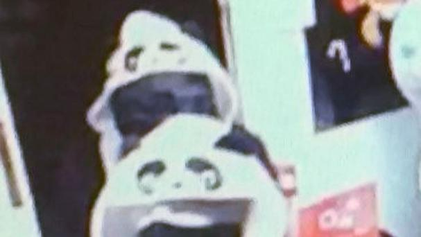 CCTV image of two people, dressed in panda onesies, who robbed a shop in Louth (Lincolnshire Police/PA)