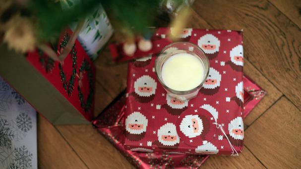 A glass of milk rests on presents underneath a Christmas tree