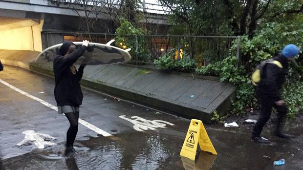A person carrying a surfboard crosses the puddle outside Drummond Central in Newcastle upon Tyne, which became an internet sensation, but has now been drained by council workmen