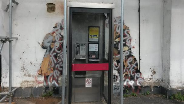 The Banksy mural targeting the issue of Government surveillance that has been vandalised with silver and red paint