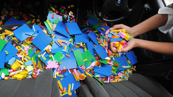 A person deposits some Lego into a BMW car in central London, during a photocall for an art project by Ai Weiwei in October 2015