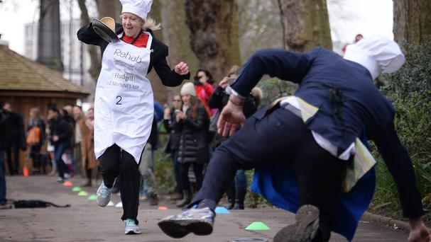 Heywood and Middleton MP Liz McInnes goes past Lord St John of Bletso as they take part the annual Rehab Parliamentary Pancake Race in Victoria Tower Gardens, London