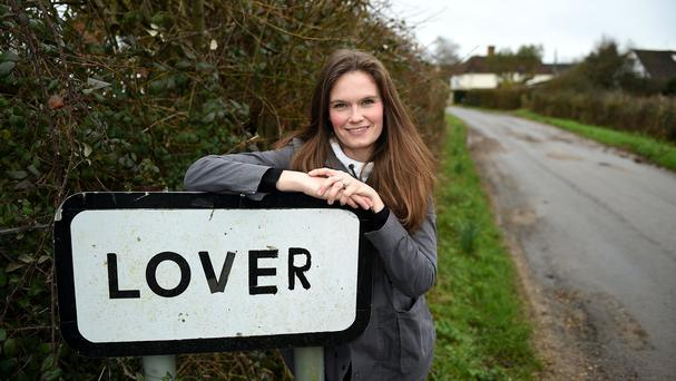 Local resident and campaigner Katie Gibbs poses next to a sign for Lover village in Wiltshire, as the residents have sent out a Valentine's Day plea for help in their bid to bring life back to their rural home