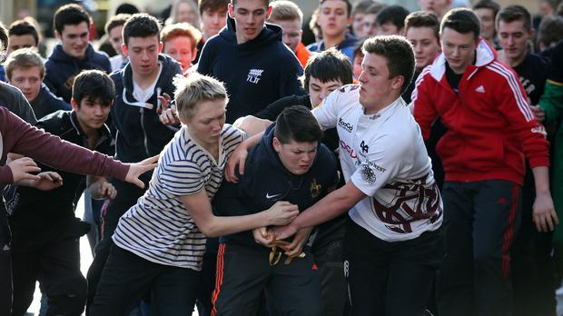 Boys tussle for the leather ball during the hand ba' event |