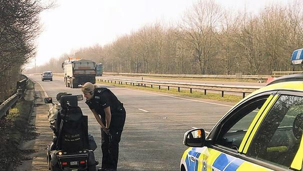 Sussex Police handout photo of PC Katie Breeds speaking to a 'very confused' 92-year-old man who found himself on his mobility scooter on the busy A2011 near Crawley, West Sussex after taking a wrong turn