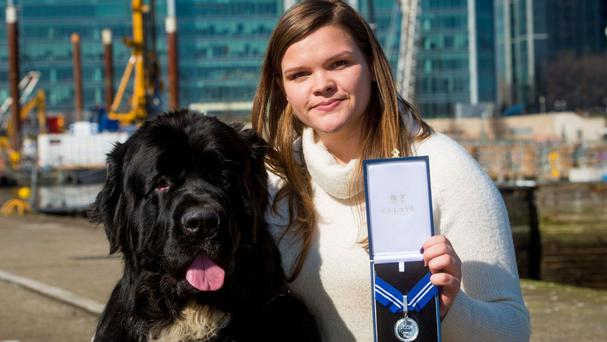 Tizz the Newfoundland dog with Ellie Bedford receiving the PDSA Order of Merit known as the animals' OBE - on behalf of his cousin Whizz who saved nine people and another dog from drowning during a decade of lifesaving (PDSA)