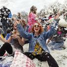 People take part in a mass pillow fight in Kennington Park in London to mark International Pillow Fight Day