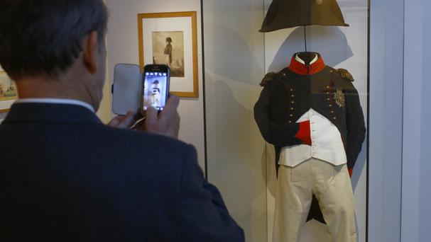 A visitor takes pictures of Napoleon's clothes at the exhibition Napoleon in St Helena in Paris (AP)