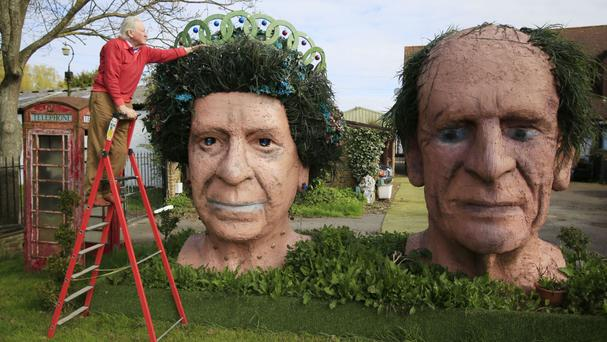 Ben Bennett, 83, tends to artificial leaves which form the hair on a terracotta head sculpture of the Queen which stands next to one of the Duke of Edinburgh in his front garden in Fifield, Berkshire