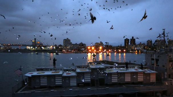 Pigeons wearing LED lights fly above their coops in a 30-minute performance (AP)