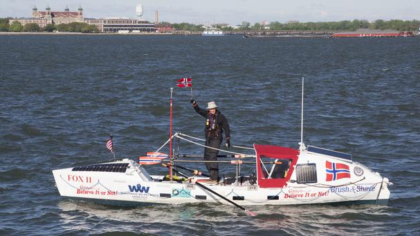 Stein Hoff, 70, waves a Norwegian flag as he passes Ellis Island (AP)
