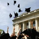 New graduates throw their mortarboards into the air at Portsmouth's Guildhall