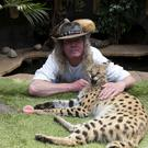 Iain Newby with his serval cat Squeaks at his home in Great Wakering, Essex