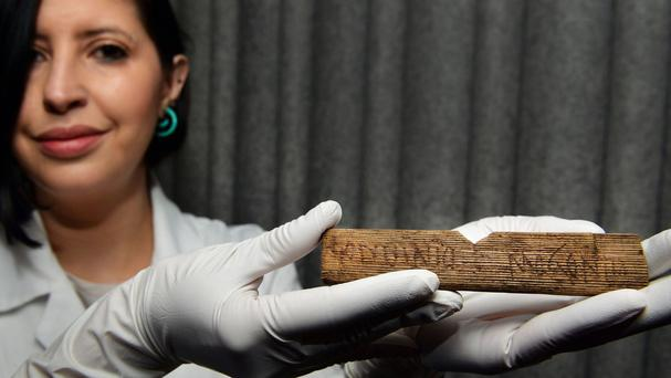 Luisa Duarte from the Museum of London holds a piece of wood with the Roman alphabet written on it in AD 60/62