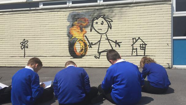 Children from Bridge Farm Primary School in Bristol copying a Banksy mural which was painted on the side of one of their classrooms during half-term