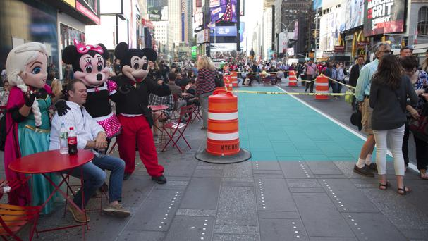 A visitor to Times Square poses for a photo with costumed characters next to an area being prepared as a colour-coded Designated Activity Zone (AP)