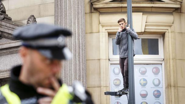 A man stands on a lamppost in City Square in Leeds, bringing traffic to a standstill