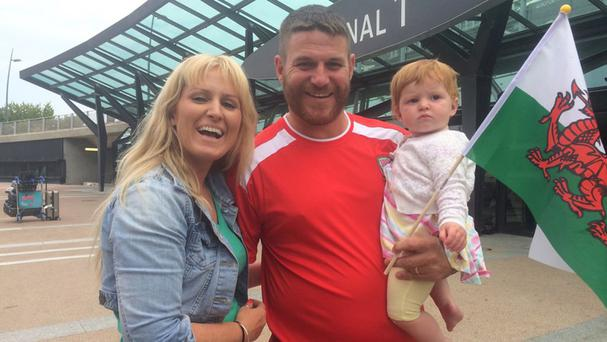 Wales football fan Ian Williams with his partner Helen Williams and their daughter Florence at Lyon airport (BBC)