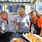 The Prince of Wales samples a curry with the Duchess of Cornwall during a visit to Penzance